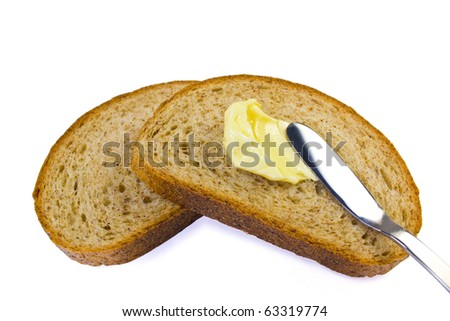 spreading butter on  sliced bread - stock photo