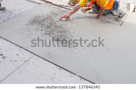 Spreading concrete for sidewalk repair - stock photo