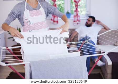 Spreading laundry in living room man in back ground, life style, family photo laundry and housekeeping concept - happy woman hanging clothes on dryer in living room Shallow depth of field