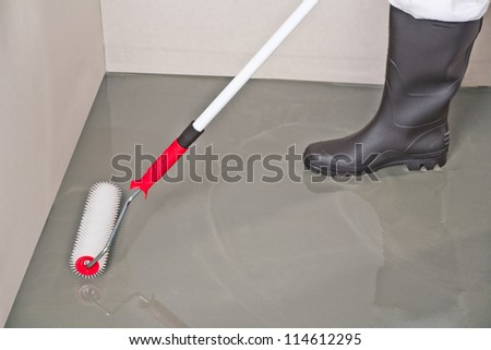 spreading self leveling compound with roller - stock photo