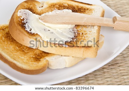 Spreading toasts by wooden knife - stock photo