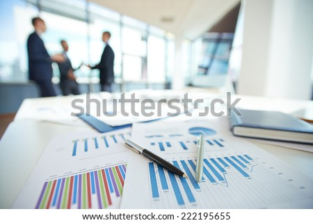 Spreadsheets with charts on office table - stock photo