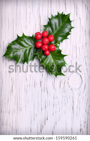 Sprig of christmas holly with red berries on vintage wooden background - stock photo