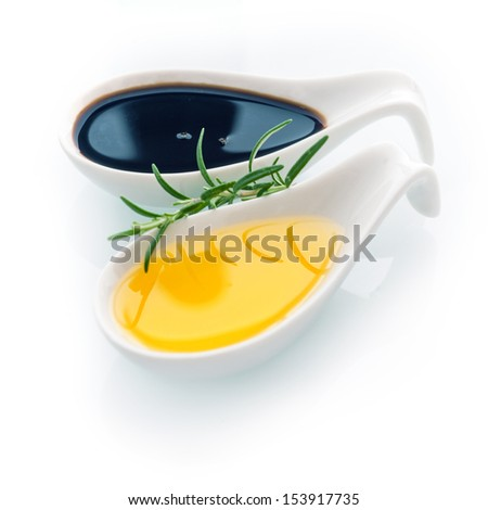 Sprig of fresh rosemary for seasoning food with golden virgin olive oil in a ceramic spoon on a white background for healthy cooking and cuisine - stock photo