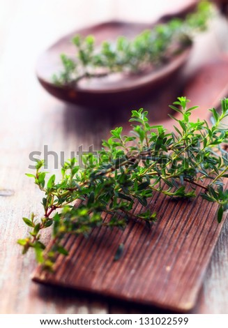 Sprig of fresh thyme lying on a rustic wooden chopping board in a country kitchen to be used as a seasoning in cooking - stock photo