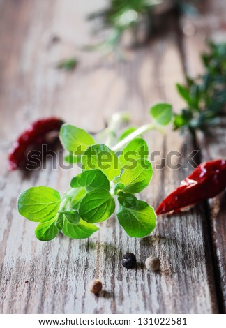 Sprig of fresh thyme lying on grunge weathered wood amidst scattered fresh herbs ready to be used as seasoning in the cooking - stock photo