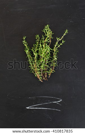 Sprigs of thyme on a black board - stock photo