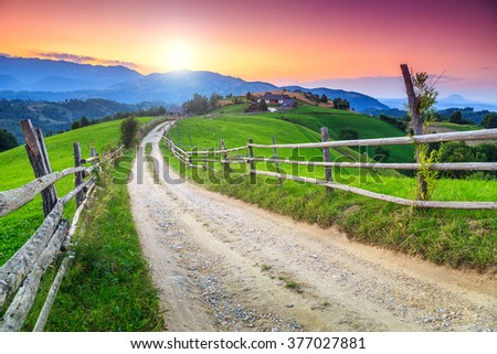 Spring alpine landscape with green fields and majestic sunset,Bran,Transylvania,Romania,Europe - stock photo