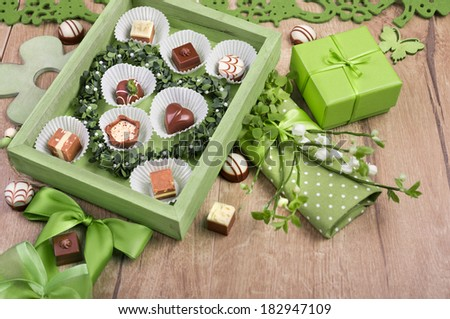 Spring arrangement with chocolate pralines, green objects and twigs - stock photo