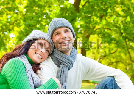 Spring autumn lovely smiling couple sitting in a park being happy in the late summer with cold weather - stock photo
