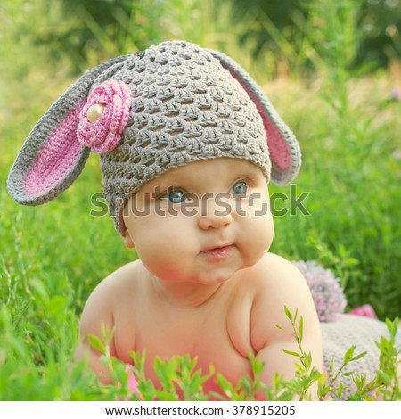Spring baby like Easter bunny in the green grass. Easter holiday concept