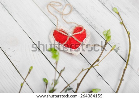 Spring background. Plushy red heart and blooming tree branches on aged white wooden planks as background - stock photo