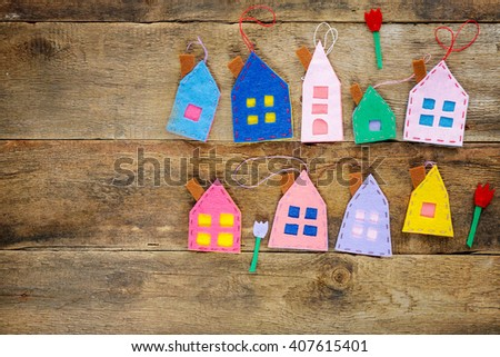 Spring background with handmade little houses and tulips over wooden background, copy space - stock photo