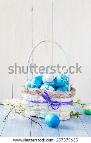 Spring basket with Easter eggs in a blue tone - stock photo