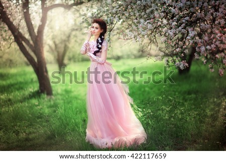 Spring Beautiful romantic brunette girl standing in blooming apple garden .Princess in pink beautiful lace dress and flowers in hair dreaming. Fairy tale and art work.Warm colors