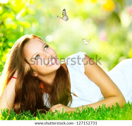 Spring Beauty Girl. Beautiful Young Woman Lying on Green Grass outdoor. Park. Meadow. Summer. Spring Girl lying on the Field. Happiness. Outdoors. Youth concept - stock photo