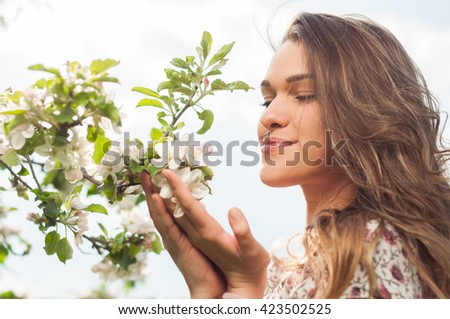 Spring beauty girl enjoying nature and sunshine in the blooming garden of apple trees - stock photo