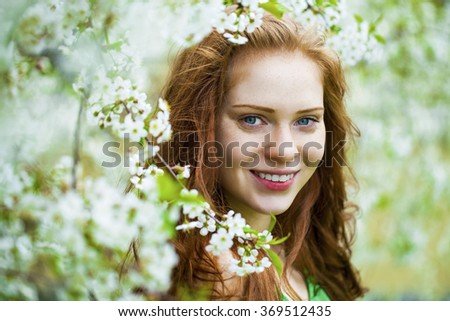 Spring beauty girl with long red blowing hair outdoors. Blooming trees. Romantic young woman portrait - stock photo