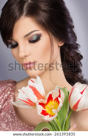 Spring beauty model studio shooting. Portrait of smiling young woman with flowers orange tulips on white background. Fashion fresh makeup. Sensual lips. Perfect skin. Tenderness. Romantic style. - stock photo
