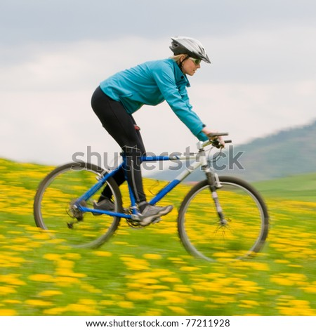 Spring bike riding - woman downhill on bike in dandelion (intentional motion blur) - stock photo