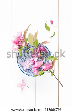 Spring - blooming twig with pink flowers in a china blue decorative bowl. White rustic wooden background. Flat lay composition (from above, top view). - stock photo