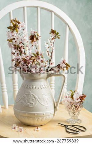 Spring blossom in antique pottery vase with scissors on rustic chair - stock photo