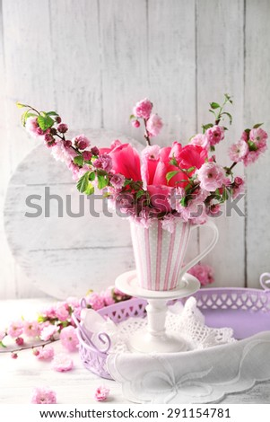 Spring bouquet in colorful mug on color wooden background - stock photo