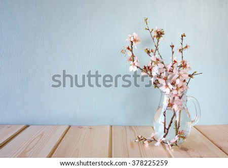 spring bouquet of flowers on the wooden table with mint background. vintage filtered image  - stock photo
