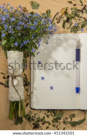 Spring bouquet of forget-me colors in the morning rays of the sun, notebook and pen on the wooden table