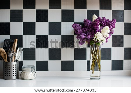 Spring bouquet of lilacs in a vase and kitchen utensils on the kitchen table by the wall, home interior - stock photo