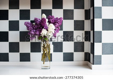 Spring bouquet of lilacs in a vase on the kitchen table by the wall, home interior