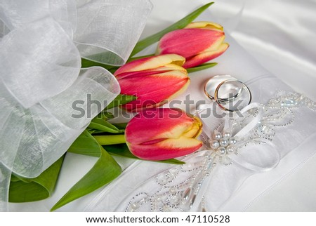 spring bridal bouquet with rings on wedding pillow - stock photo