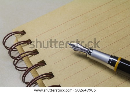 spring business man with notebook kraft sheets and feather pen black / notebook and fountain pen