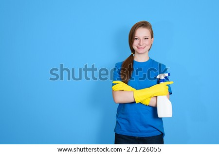 Spring cleaning. Cleaning woman with cleaning spray bottle happy and smiling. Beautiful cleaning girl isolated on blue background with copyspace.  - stock photo