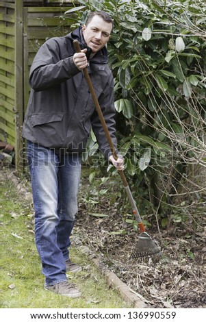 spring cleaning.  gardener at seasonal spring garden work . removing foliage in the front yard. - stock photo