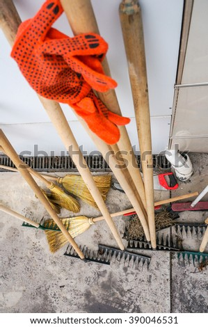 Spring cleaning with rakes and broom in an orchard concept - stock photo