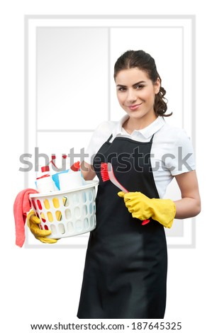 Spring cleaning Woman with black apron holding a red  Cleaning Brush in left hand  and a basket full of cleaning products in right hand. Fake window on background,white background - stock photo