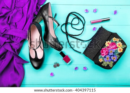 spring clothes, women's clothes - a purple dress, embroidered bag, black heels, earrings, nail polish, lipstick. turquoise wooden background, top view - stock photo