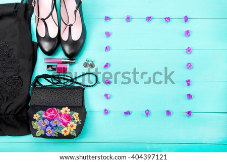 spring clothes, women's clothes - a purple dress, embroidered bag, black heels, earrings, nail polish, lipstick. turquoise wooden background, top view, frame for text - stock photo