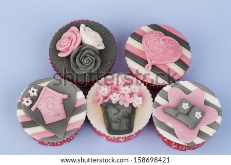 Spring decorated cupcakes in pink grey on a blue background - stock photo