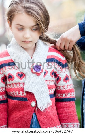 Spring fairy. Portrait of beautiful little girl with brownish blond hair and blue eyes standing outdoor on natural background. Sister makes her pigtails. - stock photo