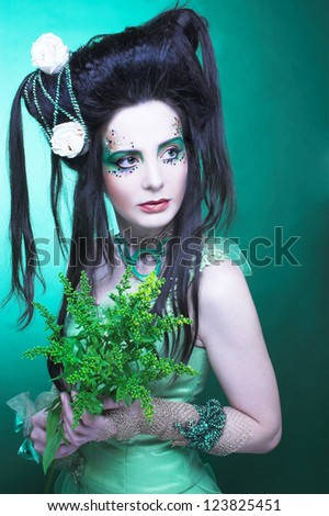 Spring fairy. Young woman in green dress and with artistic visage and hairstyle.