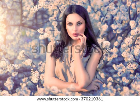 Spring fashion girl outdoors portrait in blooming trees. Beauty Romantic woman in flowers. Sensual Lady. Beautiful Woman Enjoying Nature. Romantic beauty in fantasy orchard - stock photo
