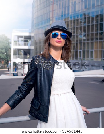 Spring fashion image of young woman wearing white dress,black leather coat and grey hat