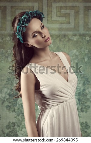 spring fashion portrait of romantic brunette woman with long hair, coloured flowers on the head and sexy white dress  - stock photo