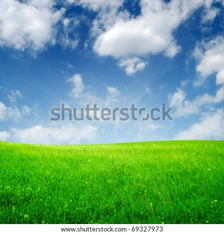 spring field and blue sky with clouds - stock photo