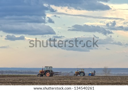 Spring field work. Farmers on tractors working in the fields, plowing and sowing. - stock photo