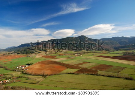 Spring fields are photographed from above. There are remote mountains and the blue sky. - stock photo
