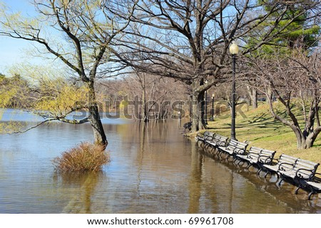 Spring floods cover a path on a sunny day in horizontal - stock photo