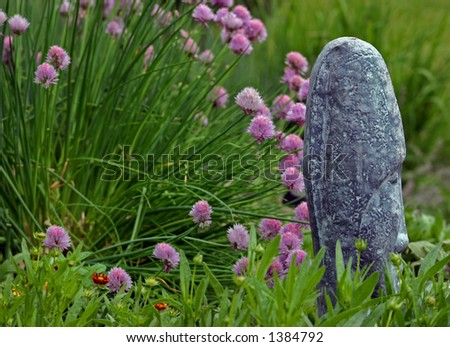 spring flowers in bloom with garden statue in forefront - stock photo